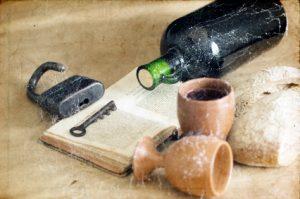 Weinflasche, Weinbecher und Buch in Staub gehüllt