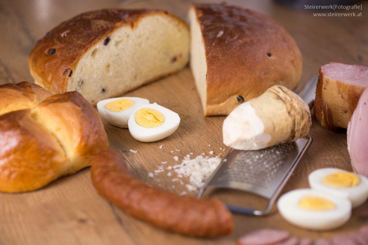 Zutaten für die Osterjause mit Osterbrot, Pinze, Eier, Schinken, Würstel und Kren
