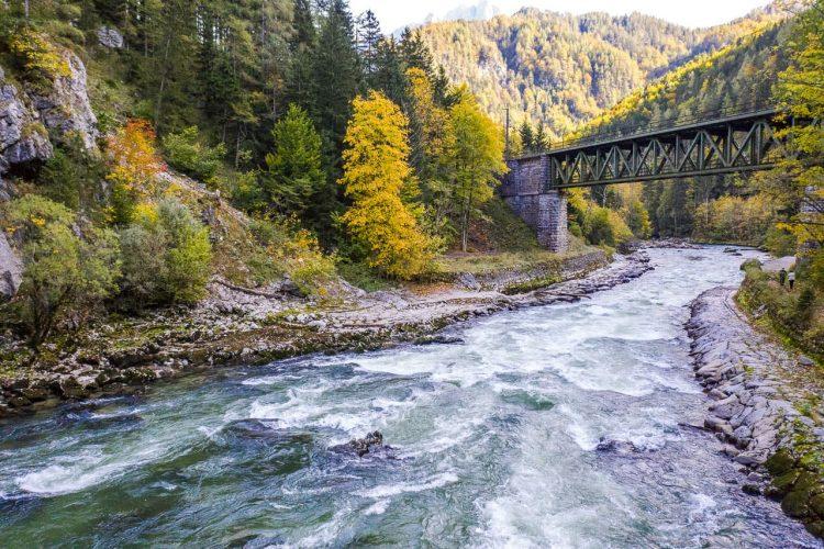 Die Enns fließt im Gesäuse unter eine Eisenbahnbrücke
